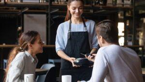Paar bezahlt im Cafe mit Mobile Payment