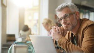 Mann sitzt im Cafe mit Laptop und schaut nachdenklich